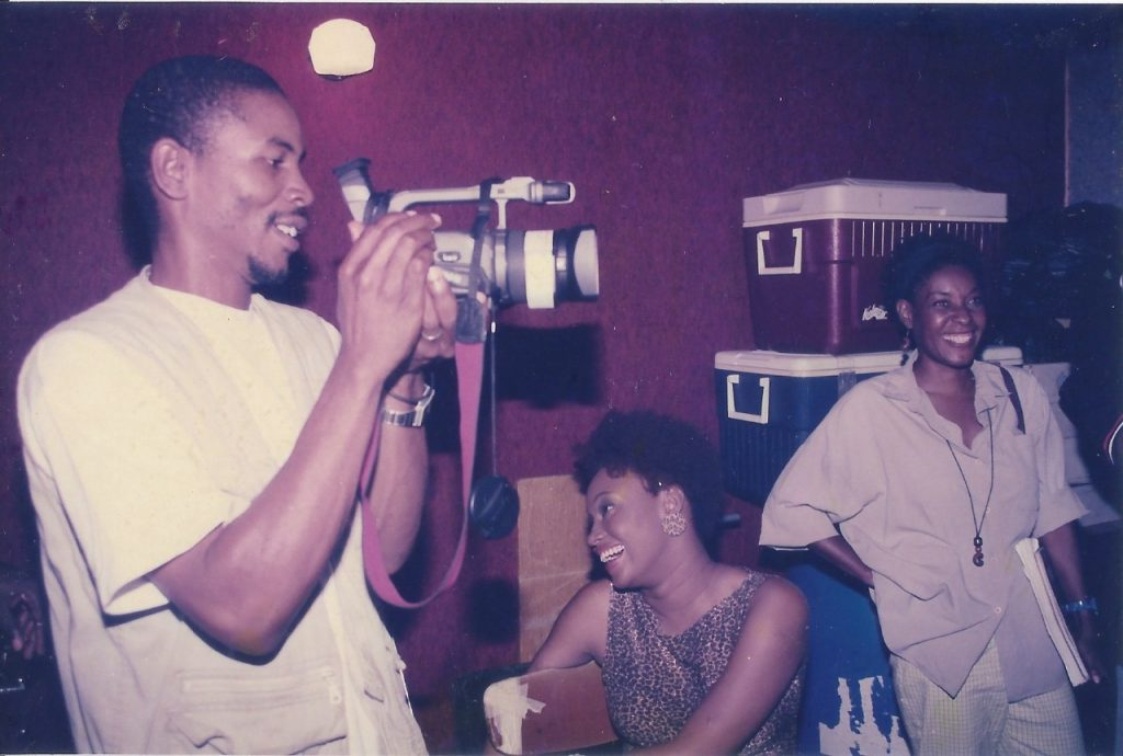 Couple sharing a light moment on set of The Sweetest Mango with film extra Dara Davis in the middle. (July 2000)